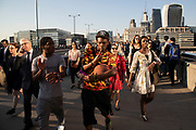 Young man carrying a basketball gestures towards the camera while crossing south on London Bridge at rush hour at the end of the working day in the financial district of the City of London, England, United Kingdom.