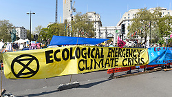 "© Licensed to London News Pictures. 22/04/2019. LONDON, UK.  Signs span the road around Marble Arch during ""London: International Rebellion"", on day eight of a protest organised by Extinction Rebellion.  Protesters are demanding that governments take action against climate change.  After police issued section 14 orders at the other protest sites of Oxford Circus, Waterloo Bridge and Parliament Square resulting in over 900 arrests, protesters have convened at the designated site of Marble Arch so that the protest can continue.  Photo credit: Stephen Chung/LNP"