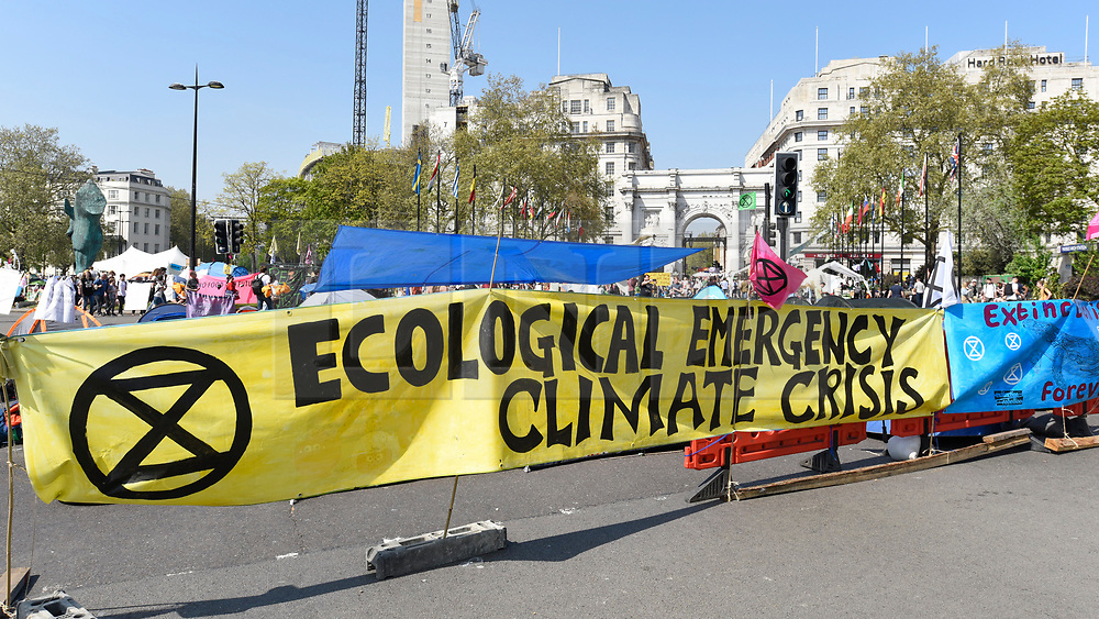 """© Licensed to London News Pictures. 22/04/2019. LONDON, UK.  Signs span the road around Marble Arch during """"London: International Rebellion"""", on day eight of a protest organised by Extinction Rebellion.  Protesters are demanding that governments take action against climate change.  After police issued section 14 orders at the other protest sites of Oxford Circus, Waterloo Bridge and Parliament Square resulting in over 900 arrests, protesters have convened at the designated site of Marble Arch so that the protest can continue.  Photo credit: Stephen Chung/LNP"""