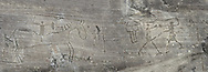 Petroglyph, rock carving, of a man on horse back with a spear and two warriors fighting with swords, carved by the ancient Camuni people in the iron age between  900-1200 BC. Rock 26-27, Foppi di Nadro, Riserva Naturale Incisioni Rupestri di Ceto, Cimbergo e Paspardo, Capo di Ponti, Valcamonica (Val Camonica), Lombardy plain, Italy .<br /> <br /> Visit our PREHISTORY PHOTO COLLECTIONS for more   photos  to download or buy as prints https://funkystock.photoshelter.com/gallery-collection/Prehistoric-Neolithic-Sites-Art-Artefacts-Pictures-Photos/C0000tfxw63zrUT4<br /> If you prefer to buy from our ALAMY PHOTO LIBRARY  Collection visit : https://www.alamy.com/portfolio/paul-williams-funkystock/valcamonica-rock-art.html