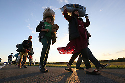 © London News Pictures. © London News Pictures. © © © London News Pictures. Migrants walk along the motorway towards Budapest after they  broke out from the camp close to the Hungarian and Serbian border town of Roszke, Hungary, September 7 2015. The UN's humanitarian agencies are on the verge of bankruptcy and unable to meet the basic needs of millions of people because of the size of the refugee crisis in the Middle East, Africa and Europe, senior figures within the UN have told the media.   Picture by Paul Hackett /LNP