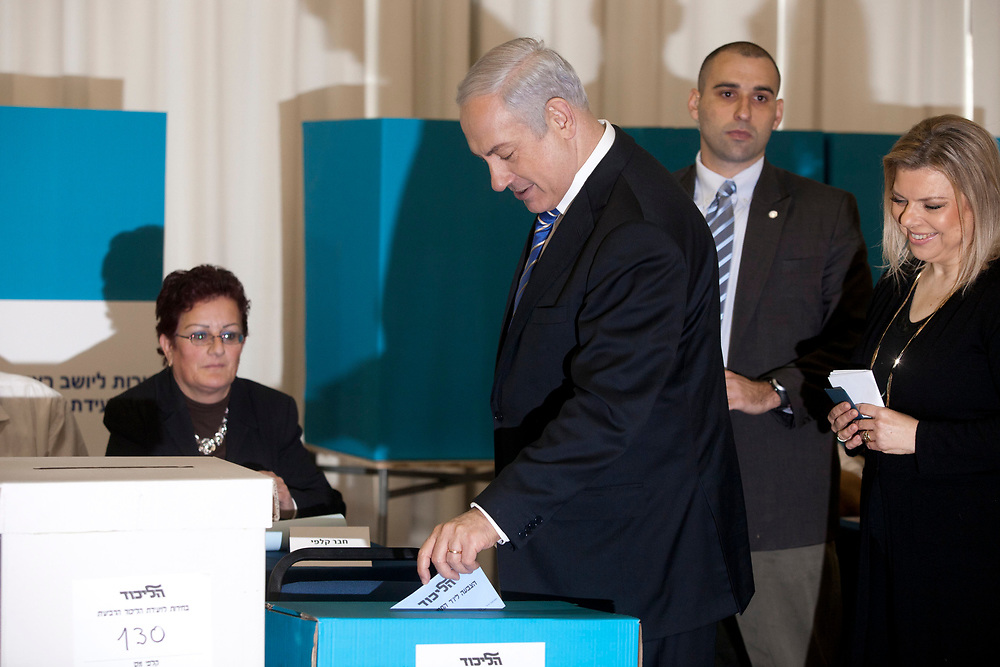 Israel's Prime Minister and Likud party leader Benjamin Netanyahu (C), casts his vote, accompanied by his wife Sara, during the Likud party primary elections, at a polling station in Jerusalem, on January 31, 2012.