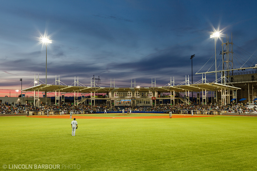 A minor league baseball game in play as seen from center field looking towards homeplate, showing the entire infield and the stands.  It's getting dark and the flood lights light up everything.
