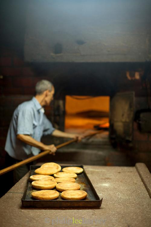 Baker preparing fresh bread in bakery, Casablanca, Morocco