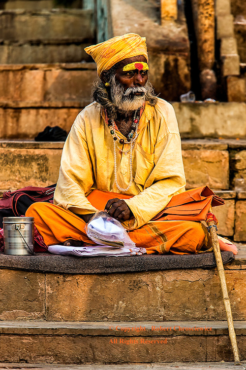 Sadhu Sitting:  A Sadhu, with both a colourful dress as well as a painted forehead, takes an early morning seat on the steps of the busy Dashaswamedh Ghat, Varanasi India.