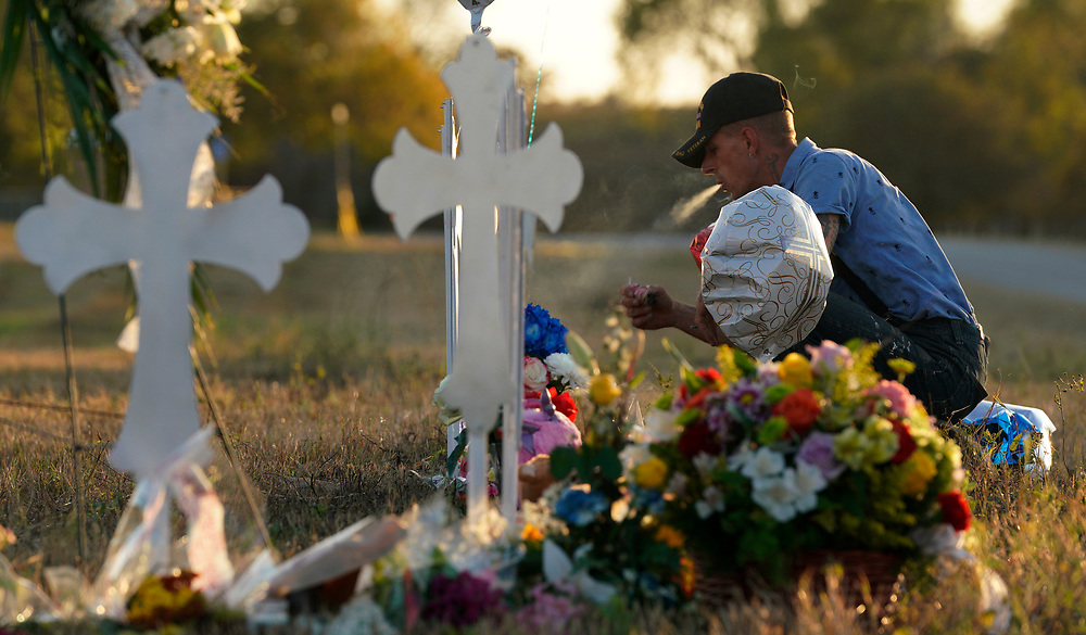 Derrick Bernaden burns sage to ward off evil at a row of crosses near the site of the shooting at the First Baptist Church of Sutherland Springs, Texas, U.S. November 7, 2017.  REUTERS/Rick Wilking