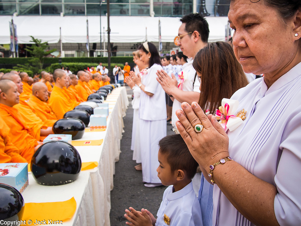 08 SEPTEMBER 2013 - BANGKOK, THAILAND: People pray before making merit and giving alms to Buddhist monks in Bangkok Sunday. 10,000 Buddhist monks participated in a mass alms giving ceremony on Rajadamri Road in front of Central World shopping mall in Bangkok. The alms giving was to benefit disaster victims in Thailand and assist Buddhist temples in the insurgency wracked southern provinces of Thailand.       PHOTO BY JACK KURTZ