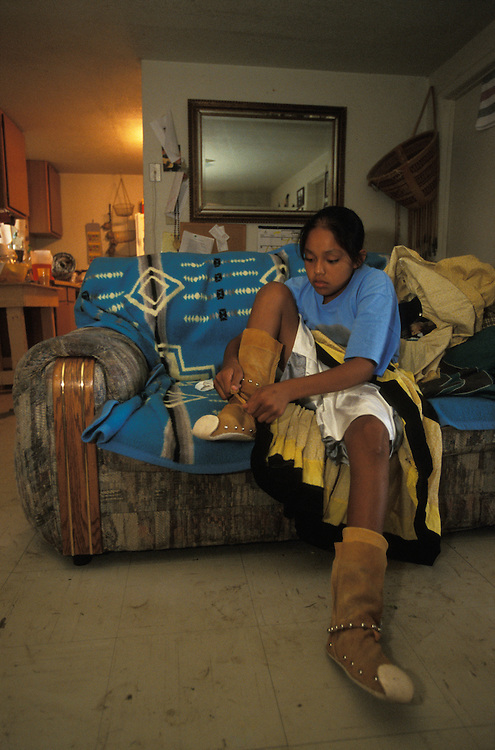 An Apache girl puts on her camp dress and moccasins in her home on the San Carlos Apache Indian Reservation in Arizona, USA. June 2004.