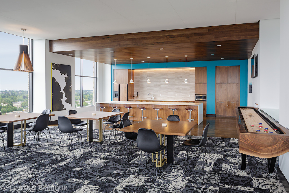 A lounge style common area in a high rise building with tables, a bar, shufflerboard. Modern design and decor.