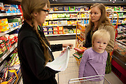 Faith D'Aluisio with Astrid Holmann and her daughter Lillith in Hamburg, Germany shopping in the Penny supermarket. They were photographed for the Hungry Planet: What I Eat project with a week's worth of food in June. Model Released.