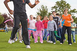 Dance teacher showing a group of children some new steps at a Parklife summer activities event,