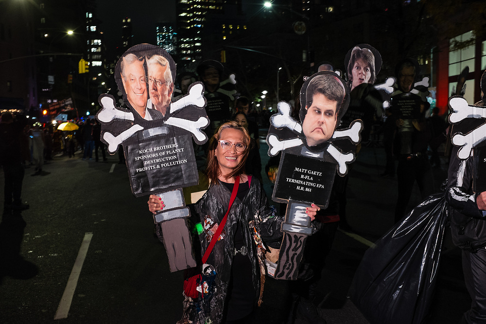 """New York, NY - 31 October 2019. the annual Greenwich Village Halloween Parade along Manhattan's 6th Avenue. A woman wears a trash bag festooned with bits of trash, and accies two signs, one lambasting the Koch brothers for """"planet destruction & pollution"""" and the other lambasting Mt Gaetz for """"terminating EPA."""""""