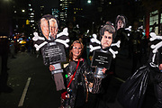 "New York, NY - 31 October 2019. the annual Greenwich Village Halloween Parade along Manhattan's 6th Avenue. A woman wears a trash bag festooned with bits of trash, and accies two signs, one lambasting the Koch brothers for ""planet destruction & pollution"" and the other lambasting Mt Gaetz for ""terminating EPA."""
