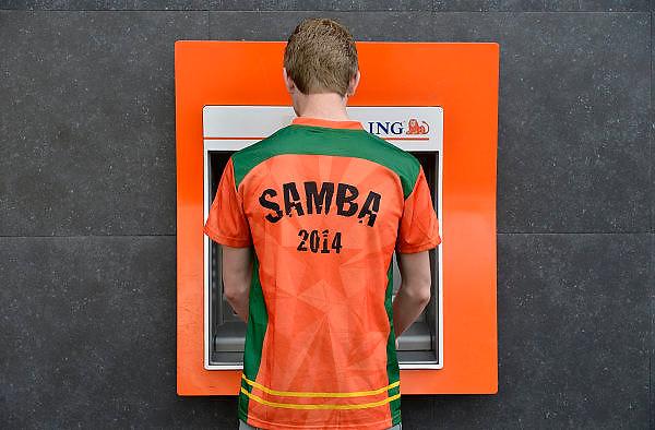 Nederland, Nijmegen, 18-6-2014Verschillende beelden van mensen als oranjesupporter die vlak voor de wedstrijd tegen Australie in de stad zijn. Een jongen haalt bij een oranje geldautomaat, pinautomaat van de ING bank nog wat contant geld. Hoij heeft een sambashirt van Heineken aan.Foto: Flip Franssen/Hollandse Hoogte
