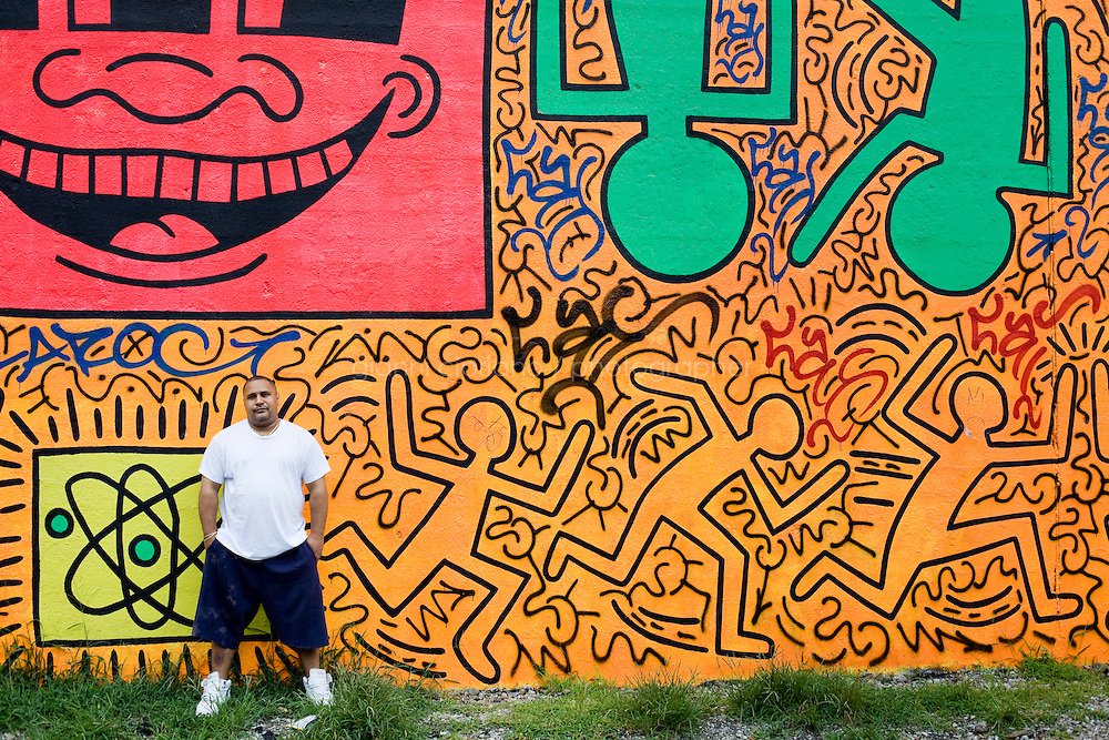 """2 August, 2008. New York, NY. Angel Ortiz, 41, a graffiti artist who collaborated with Keith Haring in the 80's, is here in front of the mural he tagged on July 22nd 2008. Angel Ortiz tagged his nickname """"LA2"""", which refers to """"Little Angel"""", on the Keith Haring mural that was reproduced on May 4th 2008, after the original 1982 graffiti was painted over. Angel Ortiz asked Clayton Patterson, an artist and gallerist, to help him tag the wall with his own artwork. Mr. Ortiz has accused the Haring Foundation of denying him credit on many of the jointly produced works.  The two artists met in 1980, when Angel Ortiz was 13 years old. Subsequently, Ortiz and Haring collaborated for several years and had joint shows. <br />  ©2008 Gianni Cipriano for The New York Times<br /> cell. +1 646 465 2168 (USA)<br /> cell. +1 328 567 7923 (Italy)<br /> gianni@giannicipriano.com<br /> www.giannicipriano.com"""