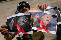 February 5, 2018 - Gaza City, Gaza Strip, Palestinian Territory - A Palestinian demonstrator burns posters of U.S. President Donald Trump during a protest to show solidarity with Palestinian prisoners held in Israeli jails, in front of Red cross office in Gaza city. (Credit Image: © Ashraf Amra/APA Images via ZUMA Wire)