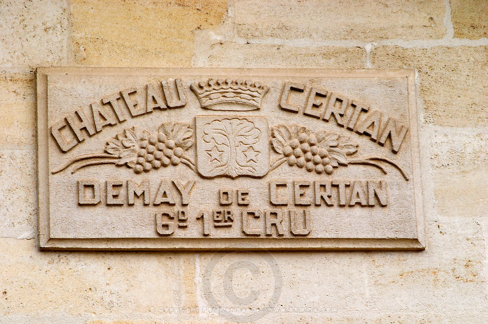 Stone plaque sign on a wall of the chateau saying Chateau Certan Demay (de May) de Certan Grand 1er Premier Cru, with grape bunches a coat of arms with a tree and two stars and a crown Pomerol Bordeaux Gironde Aquitaine France
