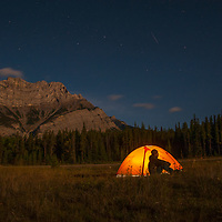 Sitting below the Big Dipper, a shooting star and Cascade Mountain, a camper admires moonlit scenes in Banff National Park, Alberta, Canada.