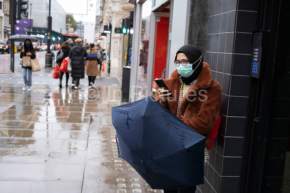 Woman using her smartphone as Londoners await the imminent second coronavirus lockdown it's business as usual in the West End with large numbers of people, some wearing face masks and some not, brave the rain on Oxford Street to go shopping on what will be the last weekend before a month-long total lockdown in the UK on 1st November 2020 in London, United Kingdom. The three tier system in the UK has not worked sufficiently, to suppress the virus, and there have have been calls by politicians for a 'circuit breaker' complete lockdown to be announced to help the growing spread of the Covid-19.