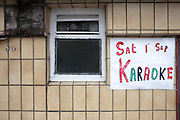Karaoke on Saturday is written in bright paint on a sheet of paper to advertise pub entertainment in Grays, Thames Gateway
