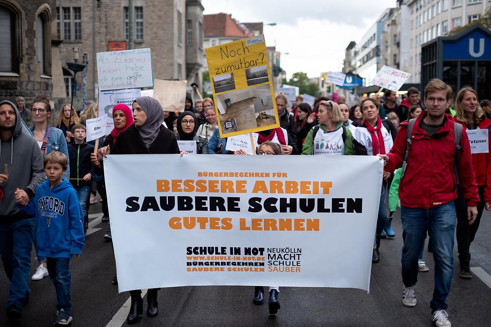"""Über 100 Eltern, Schüler Lehrer und Reinigungskräfte protestieren in Berlin Neukölln unter dem Motto """"Bessere Arbeit, saubere Schulen, gutes Lernen"""". Sie fordern eine Rekommunalisierung der Schulreinigung, da sich die Saubereit der Schultoiletten und Klassenzimmer durch Einsparmaßnahmen und Outsourcing stark verschlechtert haben soll. Demonstranten mit Banner: Bessere Arbeit - sauberer Schulen - gutes Lernen.<br /> <br /> [© Christian Mang - Veroeffentlichung nur gg. Honorar (zzgl. MwSt.), Urhebervermerk und Beleg. Nur für redaktionelle Nutzung - Publication only with licence fee payment, copyright notice and voucher copy. For editorial use only - No model release. No property release. Kontakt: mail@christianmang.com.]"""