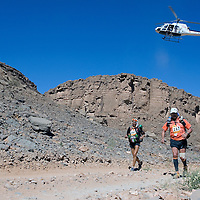 27 March 2007: #367 Chiara Tieghi of Italia (left) and #267 Francois Cresci of France run across the gorge of El Maharch during third stage of the 22nd Marathon des Sables between jebel El Oftal and jebel Zireg (20.07 miles). The Marathon des Sables is a 6 days and 151 miles endurance race with food self sufficiency across the Sahara Desert in Morocco. Each participant must carry his, or her, own backpack containing food, sleeping gear and other material.