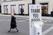 As England finishes its second Coronavirus pandemic lockdown, and London enters a Tier 2 restriction, A Londoner crosses the road behind a  visit the West End to start their Christmas high street shopping, on 2nd December 2020, in London, England. Londoner crosses the road behind a hand sanitiser post as shoppers return to the West End to start their Christmas high street shopping, on 2nd December 2020, in London, England.