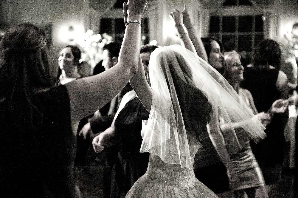 High energy dramatic B&W photo of Bride celebrating with upraised arms on dance floor at her Wedding