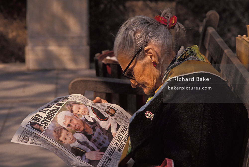An elderly woman reads a copy of a tabloid newspaper, on 16th June 1989, in London, England.