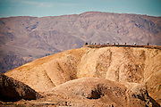 Tourists at the scenic overlook at the badlands at Zabriskie Point looking toward Golden Canyon in Death Valley National Park, Nevada, USA. Zabriskie point was once the home of twenty-mule team borax mines.