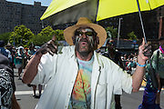 Brooklyn, NY - 18 June 2016. A man with streaked makeup and a straw hat parades under a black and yellow umbrella.