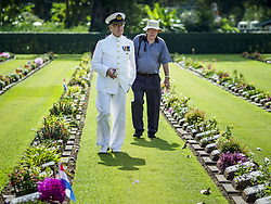 November 11, 2018 - Kanchanaburi, Kanchanaburi, Thailand - J.P. VAN DER MEULEN, left, a veteran of the Dutch Navy, walks through Kanchanaburi War Cemetery before the Rememberance Day ceremony in Kanchanaburi, Thailand. Kanchanaburi is the location of the infamous ''Bridge On the River Kwai'' and was known for the ''Death Railway'' built by Japan during World War II using allied, principally British, Australian and Dutch, prisoners of war as slave labor. There are 6,982 people buried in the cemetery, including 5,000 Commonwealth soldiers and 1,800 Dutch soldiers. November 11, 2018 marked the 100th anniversary of the end of World War I, celebrated as Rememberance Day in the UK and the Commonwealth and Veterans' Day in the US. (Credit Image: © Sean Edison/ZUMA Wire)