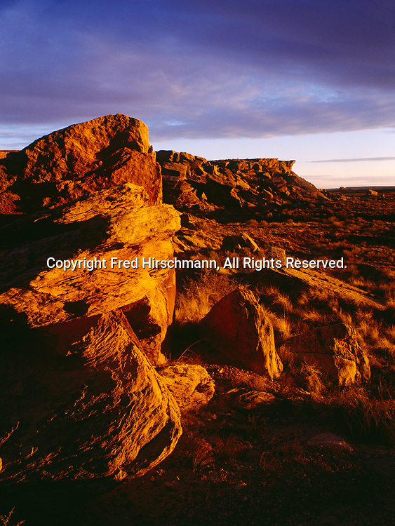 Sunset illuminating Newspaper Rock Sandstone boulders and escarpment south of the Puerco River, Petrified Forest National Park, Arizona.