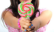 The joy of giving Teen girl offers lollipop to viewer