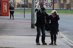 "© Licensed to London News Pictures . 10/12/2014 . Blackpool , UK . Two people hold on to one another and grab their hats in the strong wind opposite Backpool Promenade . An explosive cyclogenesis - a fast developing storm in which air pressure falls rapidly - known as a "" weather bomb "" - hits the North of England , bringing storms to the region . Photo credit : Joel Goodman/LNP"