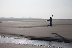 Mid adult woman jumping in mid-air on beach, Renesse, Schouwen-Duiveland, Zeeland, Netherlands