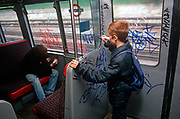 Seen from behind, two young boys tag the inside the 1980s carriage of a 1990s London Underground train, on 8th November 1989, in London, England. in 1980s London, graffiti was a persistent problem that costs the transport company network up to £3 million a year to remove. If caught, juvenile delinquents like usually escaped with only a caution because of their age - although older ones were prosecuted.