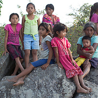 a group of Lenca children sit with an old woman on a rock in the mountains of Intibucá