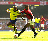 Photo: Richard Lane.<br />Arsenal v Manchester United. The FA Charity Shield 2003. 10/08/2003.<br />Silvain Wiltord and Quentine Fortune battle.