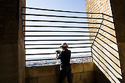 A tourist takes pictures from the top of La Giralda (cathedral tower) in Sevilla, Andalusia, Spain. The cathedral was once a great mosque, and the bell tower a minaret.