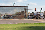 Fracking truck on main street in Kingfisher, Oklahoma passing a mural on a building in the downtown area, depicting the old West.