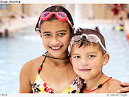 Brother and sister wearing goggles at a Seattle YMCA indoor swimming pool.