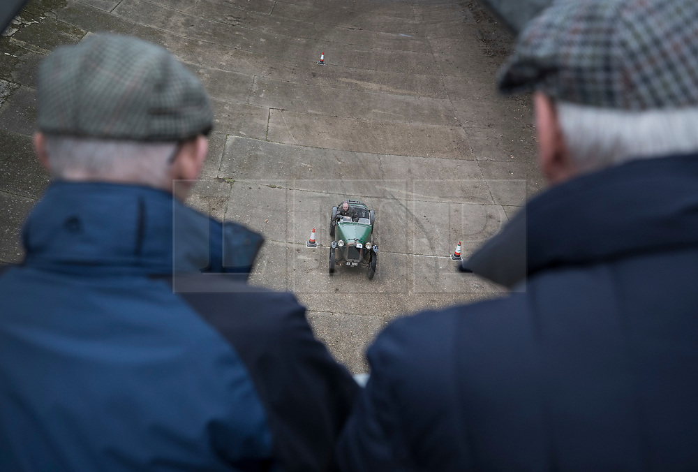© Licensed to London News Pictures. 28/01/2018. Weybridge, UK. Spectators watch from a bridge as  Jon Fleming drives a 1928 Austin Ulster Trials on the historic banked track at Brooklands Museum during The Vintage Sports-Car Club's New Year driving tests.  Photo credit: Peter Macdiarmid/LNP