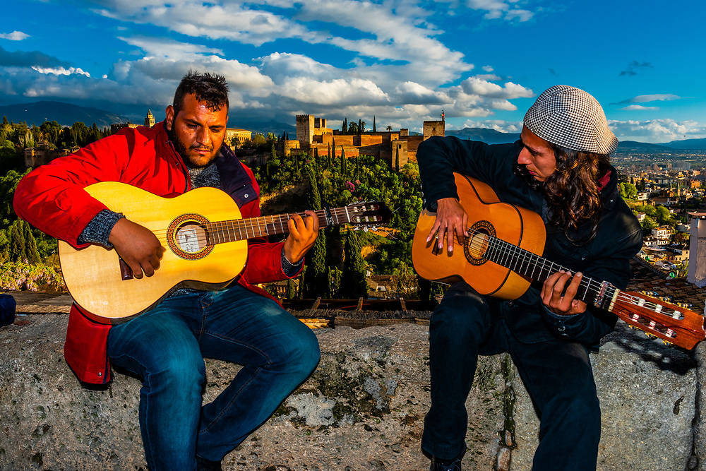 Men playing flamenco guitar with the Alhambra Palace in background, Granada, Granada Province, Spain.