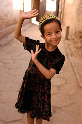 Young muslim Uyghur girl posing for photograph in old town of Kashgar in Xinjiang Province of Western China