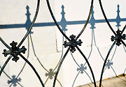 A wrought iron fence in front of a wall in New Orleans, Louisiana