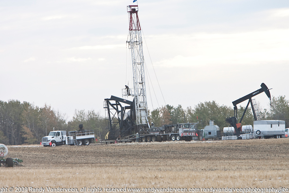 Photo Randy Vanderveen.Grande Prairie, Alberta.15/10/09.A service rig works near a pump jack on a farm east of Grande Prairie, Thursday, Oct. 15. The oil and gas sector has slowed down this past year in Alberta but there are hopes 2010 will be better for the industry.