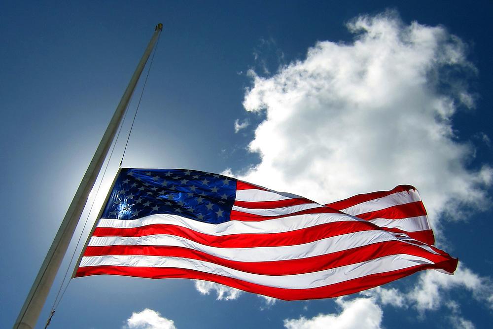 The American flag flies at half mast over the USS Arizona in Pearl Harbor, HI.