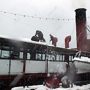 Staff of the TSS Earnslaw clear snow off the roof of the vintage steamer before sailing on Lake Wakatipu, Queenstown, after the biggest snow storm in New Zealand in the past 50 years. Queenstown, New Zealand, 16th August 2011. Photo Tim Clayton