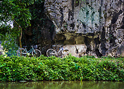 Tam Coc Scenery from the Boat. This Limestone Rock Formation provides sun shelter to a few people riding bicycles. It's hot here. RAW to Jpg